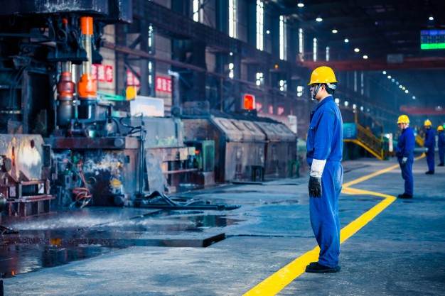 Employee standing inside a steel factory